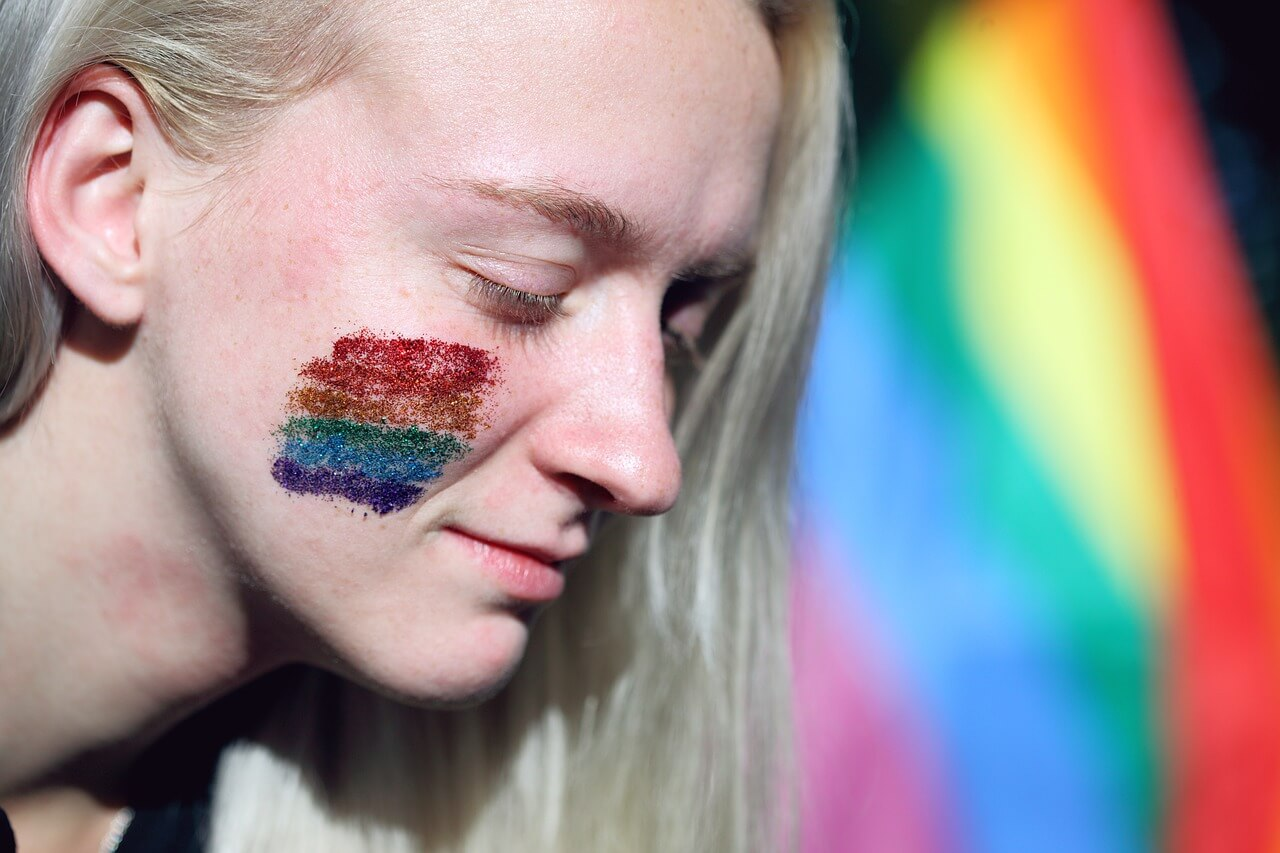 Image of a woman with a rainbow on her cheek and a pride flag in the background